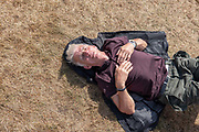 A man asleep during Latitude Festival on the 20th July 2019 in  Southwold in the United Kingdom.