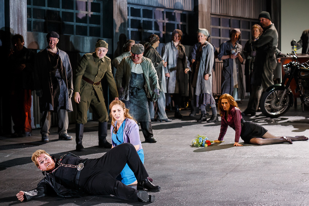 """LONDON, UK, 21 June, 2016. Foreground: Laura Wilde (in blue dress, as Jenufa) and Nicky Spence (in black, as Steva Buryja) rehearse with members of the cast for the revival of director David Alden's production of Janacek's opera """"Jenufa"""" at the London Coliseum for the English National Opera. The production opens on 23 June. Photo credit: Scott Rylander."""