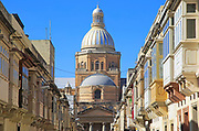 Traditional houses with balconies dome of Paola parish church, Tarxien town, near Valletta, Malta
