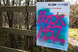 Harefield, UK. 13th February, 2021. Anti-HS2 graffiti is pictured on a sign indicating a closed public right of way on Harvil Road in the Colne Valley. Many public footpaths have been closed in the area in order to facilitate ground clearance and tree felling for the HS2 high-speed rail project.