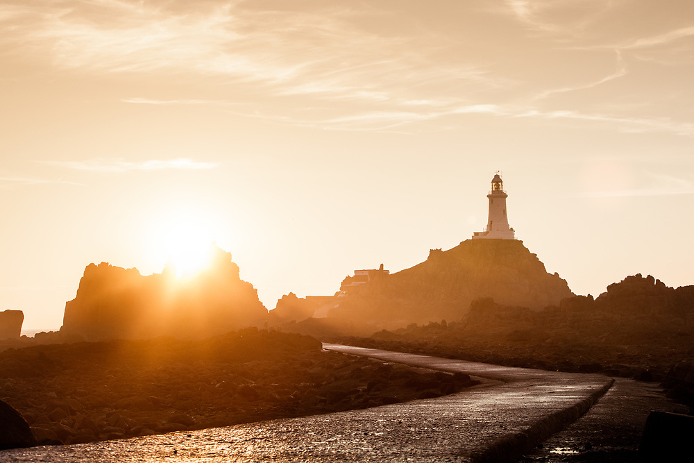 The sunsetting behind the landmark and tourist attraction Corbiere lighthouse in Jersey, Channel Islands