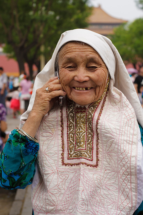 A chinese old lady talks on the phone inside the Forbidden City.