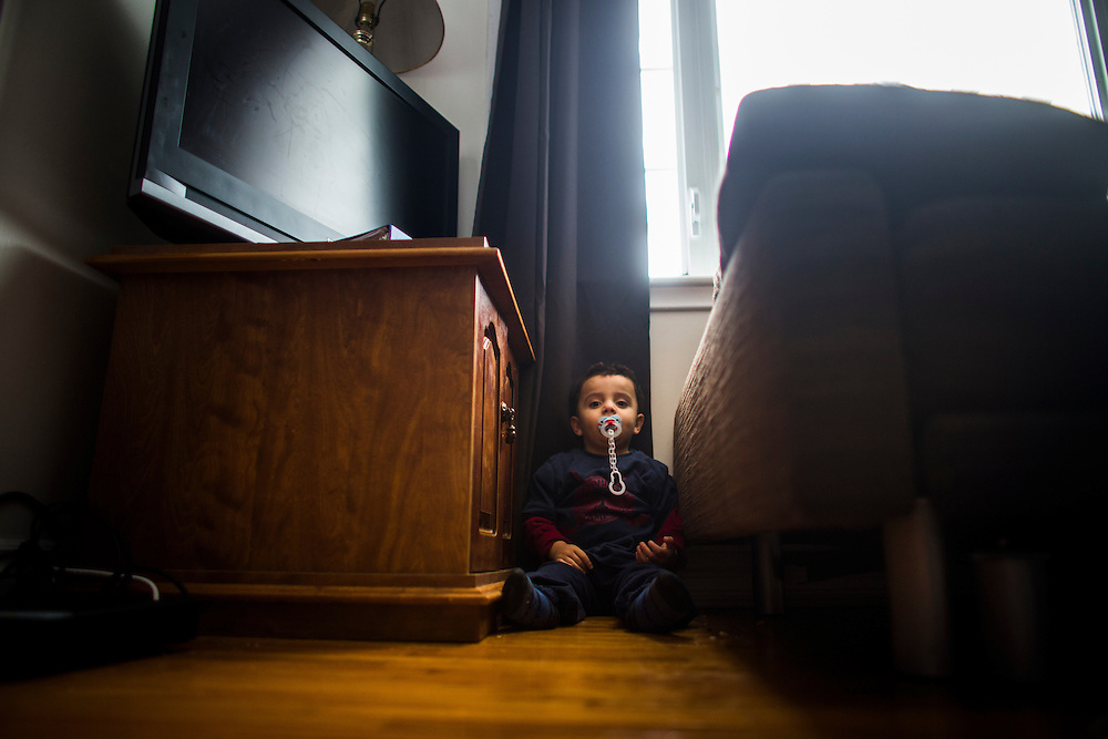 Syrian refugee Fadl Al Jasem sits between the couch on the television inside their temporary home in Picton, Ontario, Canada, Wednesday January 20, 2016.   (Mark Blinch for the BBC)