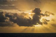 """Rise of the Mayan Sun God,"" Crespuscular Rays (Sunbeams) behind stratocumulus cloud at sunrise over the Caribbean Sea from Cancun, Quintana Roo, Yucatan Peninsula, Mexico"