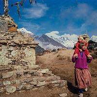 Meredith & Ben Wiltsie trek past a chorten monument  in the Khumbu region of Nepal 1986.Mts. Everest & Ama Dablam bkg