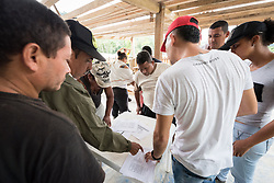 16 November 2018, San José de León, Mutatá, Antioquia, Colombia: Community members note their attendance on a sheet following a workshop on peace and reconciliation, held as part of the project De la Guerra a la Paz, in San José de León. Following the 2016 peace treaty between FARC and the Colombian government, a group of ex-combatant families have purchased and now cultivate 36 hectares of land in the territory of San José de León, municipality of Mutatá in Antioquia, Colombia. A group of 27 families first purchased the lot of land in San José de León, moving in from nearby Córdoba to settle alongside the 50-or-so families of farmers already living in the area. Today, 50 ex-combatant families live in the emerging community, which hosts a small restaurant, various committees for community organization and development, and which cultivates the land through agriculture, poultry and fish farming. Though the community has come a long way, many challenges remain on the way towards peace and reconciliation. The two-year-old community, which does not yet have a name of its own, is located in the territory of San José de León in Urabá, northwest Colombia, a strategically important corridor for trade into Central America, with resulting drug trafficking and arms trade still keeping armed groups active in the area. Many ex-combatants face trauma and insecurity, and a lack of fulfilment by the Colombian government in transition of land ownership to FARC members makes the situation delicate. Through the project De la Guerra a la Paz ('From War to Peace'), the Evangelical Lutheran Church of Colombia accompanies three communities in the Antioquia region, offering support both to ex-combatants and to the communities they now live alongside, as they reintegrate into society. Supporting a total of more than 300 families, the project seeks to alleviate the risk of re-victimization, or relapse into violent conflict.
