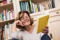 Senior woman sitting in front of bookshelf and reading, Munich, Bavaria, Germany