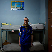 An Afghan National Police (ANP) cadet stands beside is bed at a dorm in the Afghan Nacional Police Academy in Kabul.