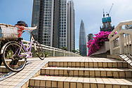 A woman pushes her bicycle up a ramp on a pedestrian overpass in Shenzhen, China. (September 6, 2019)
