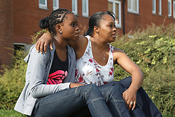Mother and daughter sitting in gardens of housing estate. Cleared for Mental Health issues.