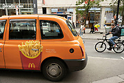 McDonalds medium fries emblazoned on the side of an orange taxi on 25th May 2021 in London, United Kingdom. McDonalds Corporation is an American fast food company, founded in 1940.