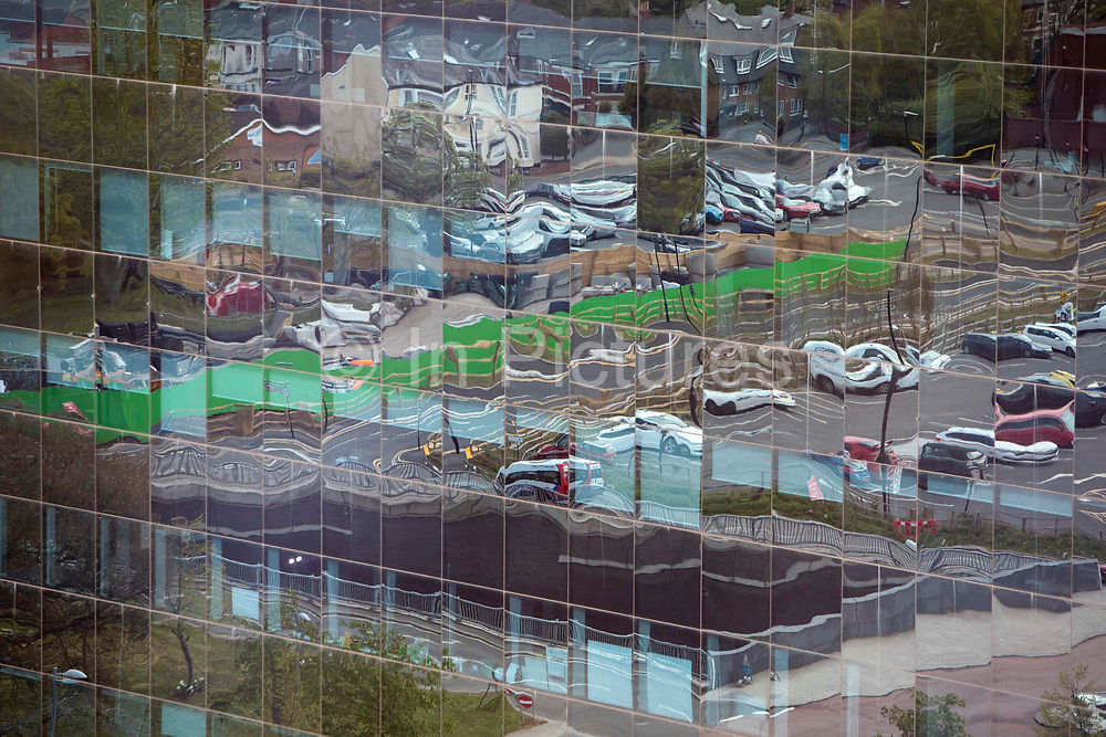 The reflective windows of a building outside Coventry Railway station on the 28th of April 2021, Coventry, United Kingdom. The train station in Coventry is currently being redeveloped as part of an £82 million project for the Coventry UK City of Culture 2021.