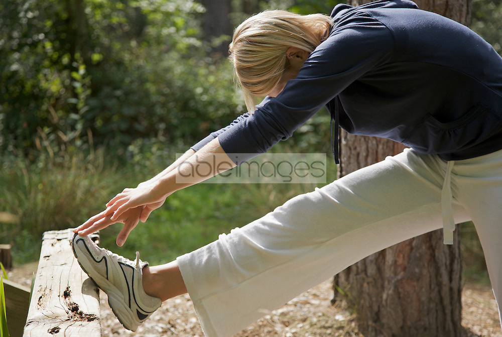 Young woman in a forest stretching her leg over a wooden beam and touching her foot
