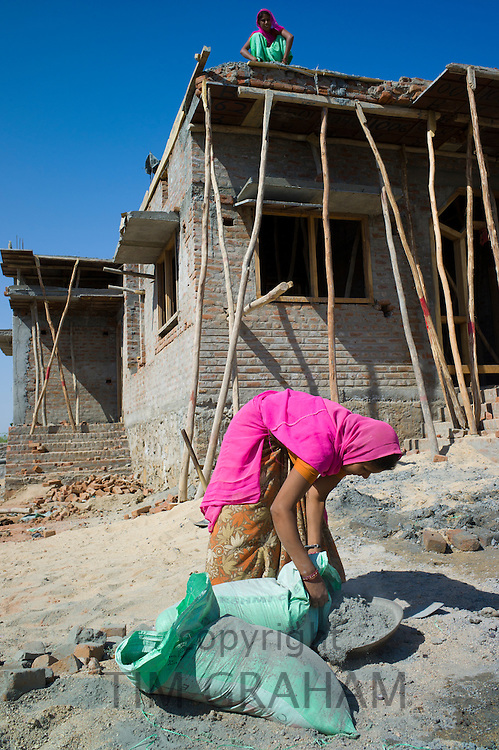 Indian woman in sari mixing cement while working on construction site at Khore village in Rajasthan, Northern India