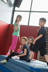 Children playing on a pile of sport mats in sports hall, Munich, Bavaria, Germany