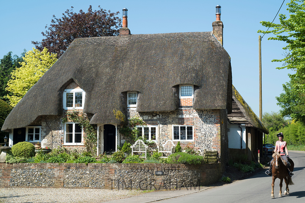 Horse rider passes typical English thatched cottage of brick and flint construction in Ramsbury, Wiltshire, UK