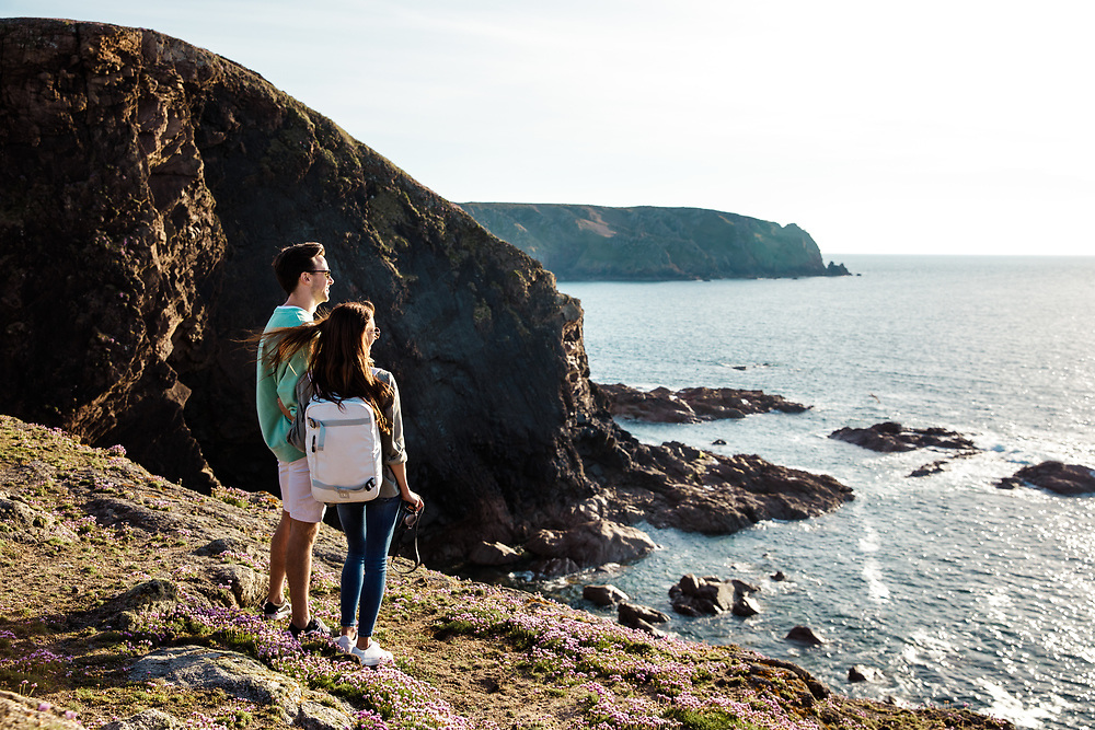 Couple walking on the cliff paths and headland near Plemont and enjoying the views out to sea in Jersey Channel Islands on a Spring day