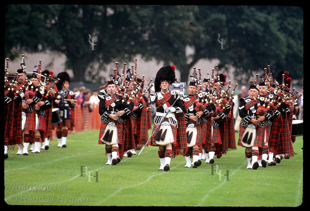 Pipe band marches across soccer field during performance at the Highland Games; July, Inverness. Scotland