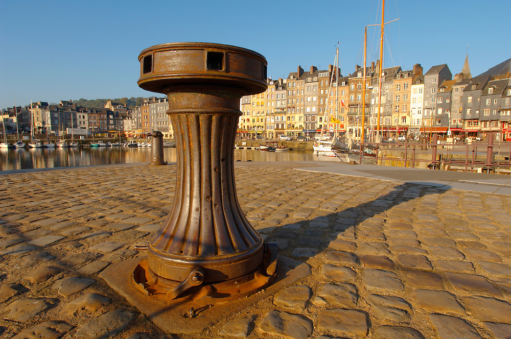 old Capstan with harbour scene with yaughts and harbour restaurants. Honfleur, Normandy, France. . Honfleur is especially known for its old port, characterised by its houses with slate-covered frontages, painted many times by artists, including in particular Gustave Courbet, Eugène Boudin, Claude Monet and Johan Jongkind, forming the école de Honfleur (Honfleur school) which contributed to the appearance of the Impressionist movement. .<br /> <br /> Visit our FRANCE HISTORIC PLACES PHOTO COLLECTIONS for more photos to download or buy as wall art prints https://funkystock.photoshelter.com/gallery-collection/Pictures-Images-of-France-Photos-of-French-Historic-Landmark-Sites/C0000pDRcOaIqj8E