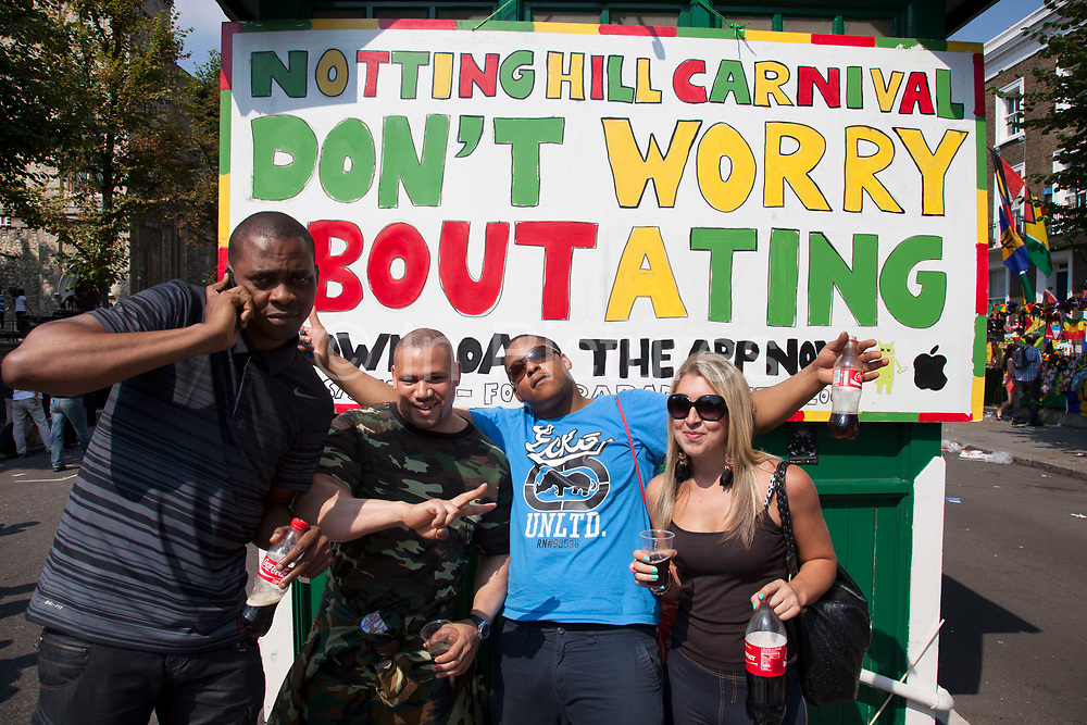 The 49th Notting Hill Carnival in West London. A celebration of West Indian / Caribbean culture and Europe's largest street party, festival and parade. Revellers come in their hundreds of thousands to have fun, dance, drink and let go in the brilliant atmosphere. Sign reads 'Don't worry 'bout a ting'.