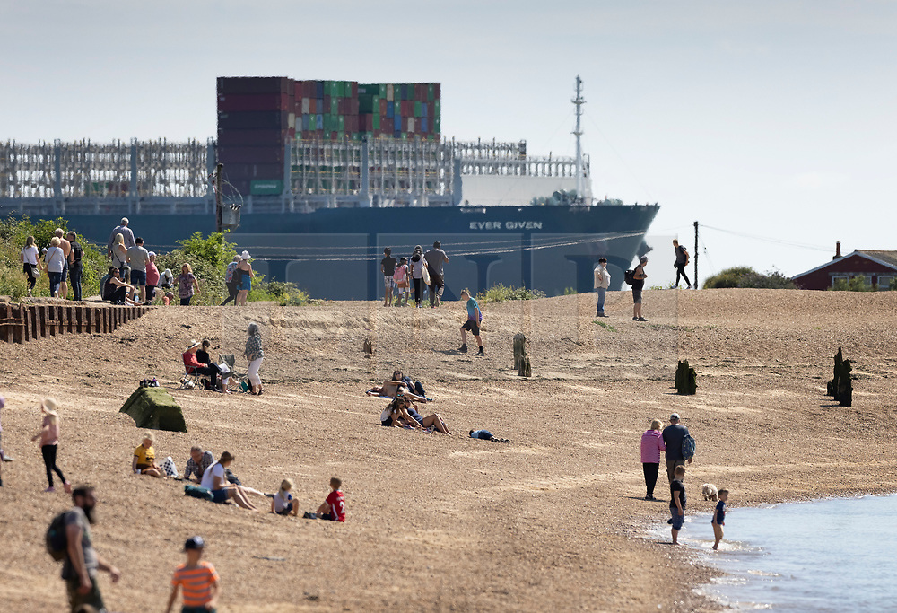 © Licensed to London News Pictures. 03/08/2021. Felixstowe, UK. The container ship 'Ever Given' comes into view for beach goers as she arrives at the port of Felixstowe in Suffolk. The giant 400 metre long cargo ship became stuck in the Suez Canal in March causing worldwide delays to trade and was only released by the Egyptian authorities after an agreement was reached over a £655m compensation claim. Photo credit: Peter Macdiarmid/LNP