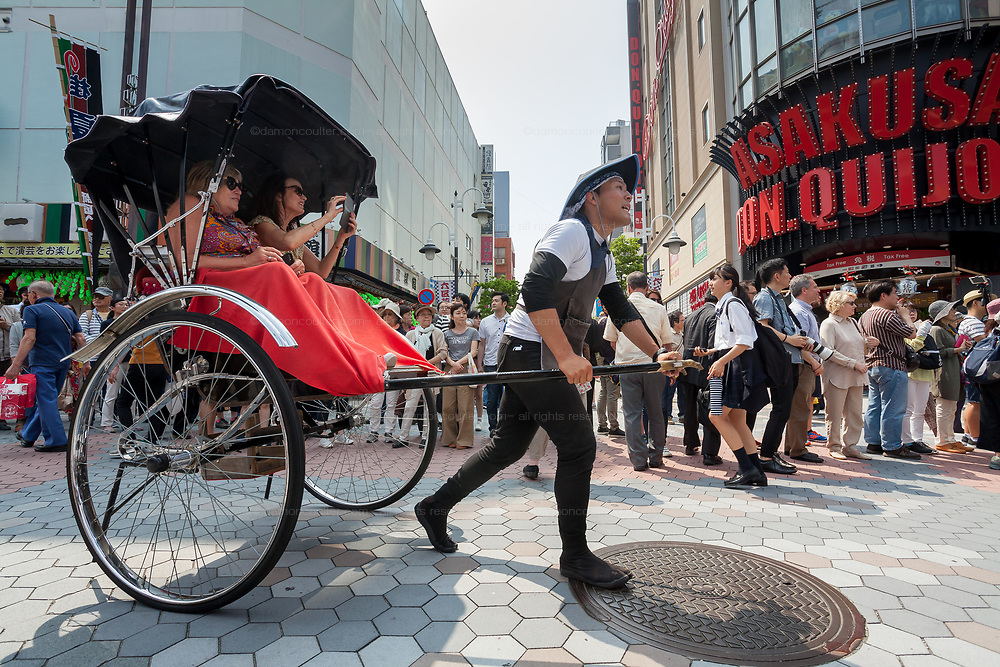 Western tourists sit in a sight-seeing rickshaw in Asakusa, Tokyo, Japan. Friday May 18th 2018.