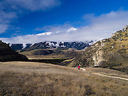 A woman walks towards the Cave Stream Overlookfor a  view of the Torlesse Range, New Zealand.