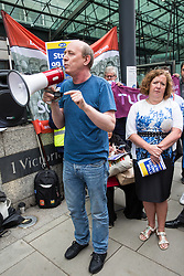 London, UK. 15 July, 2019. Sandy Nicoll of UNISON addresses catering and cleaning staff belonging to the PCS trade union and outsourced to work at the Department for Business, Energy and Industrial Strategy (BEIS) via contractors ISS World and Aramark on the picket line outside the Government department after walking out on an indefinite strike for the London Living Wage, terms and conditions comparable to the civil servants they work alongside and an end to outsourcing.