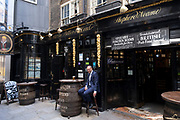 Gentleman sitting outside The Old Dr. Butlers Head pub in the City of London on 11th August 2021 in London, United Kingdom. Old Doctor Butlers Head is a pub in Masons Avenue, London EC2. The pub was named after the physician William Butler, a doctor at the court of James I. Butler is credited with inventing the medicinal drink Dr Butler's purging ale, which became popular in 17th-century England. The pub is a Grade II listed building, approximately dating back to the early 19th century.
