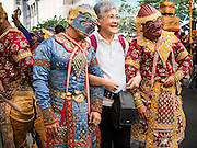 "14 JANUARY 2015 - BANGKOK, THAILAND:  A tourist poses for pictures with men in the costumes of the Thai monkey army, a popular character from Thai mythology, during the 2015 Discover Thainess parade. The Tourism Authority of Thailand (TAT) sponsored the opening ceremony of the ""2015 Discover Thainess"" Campaign with a 3.5-kilometre parade through central Bangkok. The parade featured cultural shows from several parts of Thailand. Part of the ""2015 Discover Thainess"" campaign is a showcase of Thailand's culture and natural heritage and is divided into five categories that match the major regions of Thailand – Central Region, North, Northeast, East and South.    PHOTO BY JACK KURTZ"