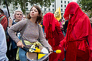 Climate change protest art group The Red Brigade perform in Whitehall on 7th October, 2019 in London, Untited Kingdom. Extinction Rebellion plan to occupy 12 sites situated around key Government locations around Westminster for two weeks to protest against climate change.