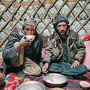 """Wakhi men drink tea in a yurt. Guiding and photographing Paul Salopek while trekking with 2 donkeys across the """"Roof of the World"""", through the Afghan Pamir and Hindukush mountains, into Pakistan and the Karakoram mountains of the Greater Western Himalaya."""