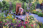 Charlie Bloom clears the pool in her Brilliance in Bloom garden - Press day at The RHS Hampton Court Flower Show.