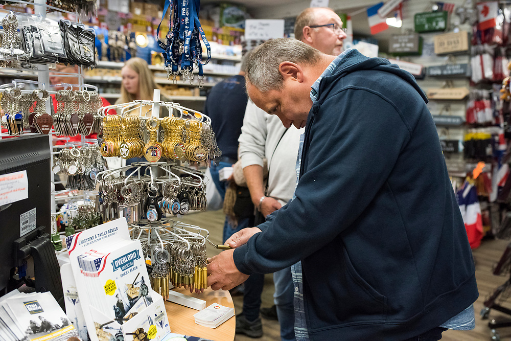 May 30, 2019, Sainte-Mère-Église, Normandy, France. A man looks at souvenirs of D-Day in the form of bullets in a local gift shop. The 75th anniversary of D-Day and Battle of Normandy commemoration is a tourist attraction.   <br /> 30 Mai 2019, Sainte-Mère-Église, Normandie, France. Un touriste regarde des souvenirs du débarquement en forme de balles dans une boutique. La bataille de Normandie est  une attraction touristique.