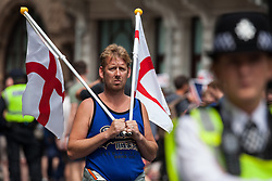 London, UK. 9th June, 2018. A supporter of Tommy Robinson, former leader of the far-right English Defence League, holds two St George flags on the fringes of the March for Tommy Robinson outside Downing Street.