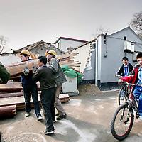China,Beijing ,13 maart 2008..Chinese bewoners, fietsende schoolkinderen en werklieden in een gerenoveerde Huton (oud buurtje) in de oude stadswijk van Beijing..Dit is 1 van de weinig overgebleven Hutons van Beijing. De meeste oude wijkjes zijn met de grond gelijk gemaakt en hebben plaats gemaakt voor grote hogenieuwe kantoorgebouwen en flats..Met het vooruitzicht op de Olympische Spelen in augustus van dit jaar zijn enkele overgebleven Hutons gerenoveerd speciaal voor de toeristen.