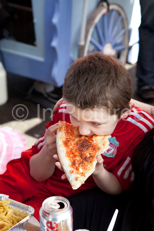 Kiefer (8, wearing a red Liverpool Football Club kit) spending a day out together in Camden Town, North London. His family can afford to have a simple lunch of pizza in the food market. Louise (his mother) is on various benefits to help support her family income, and housing, although recent government changes to benefits may affect her family drastically, possibly meaning they may have to move out of London. Louise Ryan was born on the Wirral peninsula in 1970.  She moved to London with her family in 1980.  Having lived in both Manchester and Ireland, she now lives permanently in North London with her husband and two children. Through the years Louise has battled to recover from a serious motorcycle accident in 1992 and has recently been diagnosed with Bipolar Affective Disorder. (Photo by Mike Kemp/For The Washington Post)