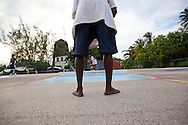 """Originating in Barbados in the 1930s, Road Tennis is played in on the back streets and roads of the country or now in permanent courts, such as the ones in Oistins and Speightstown.  The game is played on a 10x20 foot court and the """"net"""" is an 8 inch by 10 foot piece of wood.  It has the same rules as table tennis (ping pong) and is a 21 point game.  It uses hand hewn rackets made largely from plywood and tennis balls that have had the fur removed.  It is the only endemic sport to Barbados and is wildly popular among the local population.  Pictured here are the road tennis courts at the Bush Hall Community Center.  An old windmill sits on the property."""