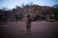 A child stands in front of the cavea his community fled to after their town was destroyed by SAF in the Nuba mountains. Starvation and bombings have seperated thousands of children from their families,