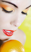 beautiful caucasian woman portrait holding a mandarine studio on yellow background
