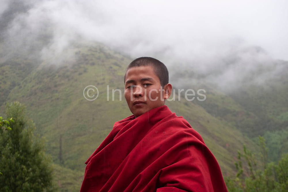 Portrait in the rain of a proud Tibetan monk in red robes at Shi Zi Shan, Lion Mountain, near the small settlement of Li Ge on Lugu Lake, Yunnan, China. Enveloped in low cloud behind him, he is from the nearby temple.