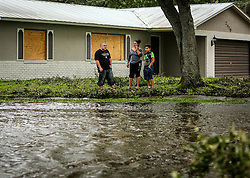 Kissimmee, Fla. residents Robert Gonzalez, his wife Maria and son David, 10, survey the flooded Town & Country Drive in front of their home, which is located on Sweetbriar Court where it meets Town & Country, on Monday, September 11, 2017. They said they had a little water get into their garage, but it quickly receded and there was no damage. Photo by Orlando Sentinel/TNS/ABACAPRESS.COM
