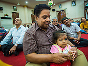 17 AUGUST 2014 - BANGKOK, THAILAND:  A man and his daughter at Krishna Janmashtami services at the Vishnu temple in Bangkok. Krishna Janmashtami is the annual celebration of the birth of the Hindu deity Krishna, the eighth avatar of the Hindu god Vishnu. It is celebrated by Hindus in Thailand. There are about 53,000 Hindus in Thailand, most originally from India, but many Hindu deities are highly revered by Thai Buddhists and Hindu holy days are observed by many Thai Buddhists.      PHOTO BY JACK KURTZ