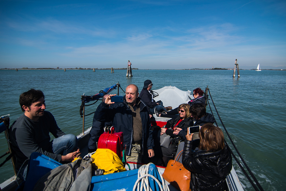 VENICE, ITALY - APRIL 2018. <br /> Tourists takes pictures and enjoy the sailing in the Venetian lagoon. Before reaching Emiliano, a moecante (crabs fisherman), tourists could see the island of Burano, that is on the way.