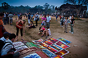 Tourists look at local artist work in Angkor Wat in Cambodia.<br /> Angkor is one of the most important archaeological sites in South-East Asia. Stretching over some 400 km2, including forested area, Angkor Archaeological Park contains the magnificent remains of the different capitals of the Khmer Empire, from the 9th to the 15th century.