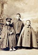 little children wearing capes in vintage studio portrait Japan