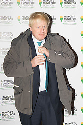 Halcyon Gallery, London, November 24th 2015. Mayor of London Boris Johnson joins celebrities and business leaders at Mayfair's Halcyon Gallery where pictures from a book showcasing London's true colours will be sold to raise money for the Mayor's Fund For London, which helps disadvantaged youths gain a foothold on the employment ladder. PICTURED: Mayor of London Boris Johnson reluctantly poses for a picture after arriving on his bike.