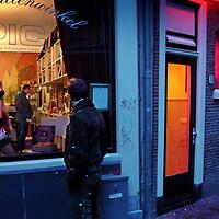 Nederland,Amsterdam ,2 december 2005..Passant kijkt in etalage wallenwinkel PIC (Prostitutie Informatie Centrum) op de wallen. Prostitutie. Wallen. Hoeren. Hoerenlopers. Hoerenbuurt. Redlight District .Lingerie. Betaalde liefde. peeskamer. De Wallenwinkel../HH