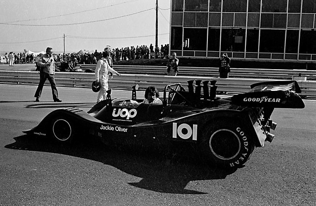 1974 Can-Am champion Jackie Oliver, pursued by veteran reporter Chris Ekonomaki (with microphone), walks along with his championship-winning Shadow DN4 to run some demonstration laps prior to the 1974 US Grand Prix at Watkins Glen. The Can-Am series had been abandoned earlier that year, the end of a grand era.