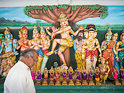 05 JUNE 2015 - KUALA LUMPUR, MALAYSIA:  A man walks past Hindu art work in Sri Mahamariamman Temple, the oldest functioning and most important Hindu temple in Malaysia. The principal deity in the temple is Mariamman,  a deity that is popularly worshipped by overseas Indians, especially Tamils, because she is looked upon as their protector during the sojourn to foreign lands. Mariamman is a manifestation of the goddess Parvati, an incarnation embodying Mother Earth with all her terrifying force. She is associated with disease and fever and protects her devotees from unholy or demonic events.    PHOTO BY JACK KURTZ